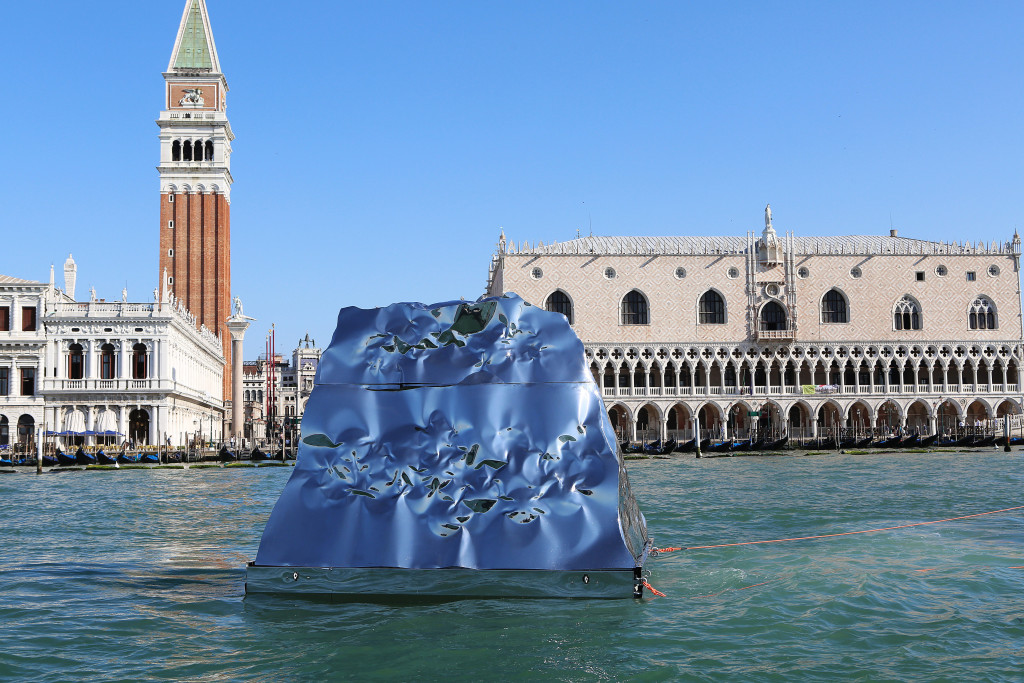Italian-Albanian artist Helidon Xhixha presents new Installations at the Syrian Arab Republic Pavilion, San Servolo island. New and unexpected artworks highlighting environmental subjects and exploitation of resources. Xhixha will unveil a steel mega-iceberg in the middle of the lagoon at the 56th Venice Biennale. Shown in front of St Marks Sqaure and travelling along the grand canal under The Rialto Bridge. Copyright Alex Maguire Photography